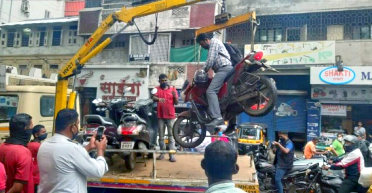Pune Traffic Police officials tow bike with the owner sitting on it