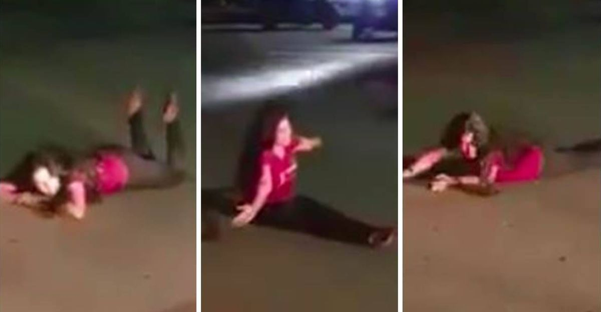 Allegedly drunk woman lies down on road, & tries to block traffic